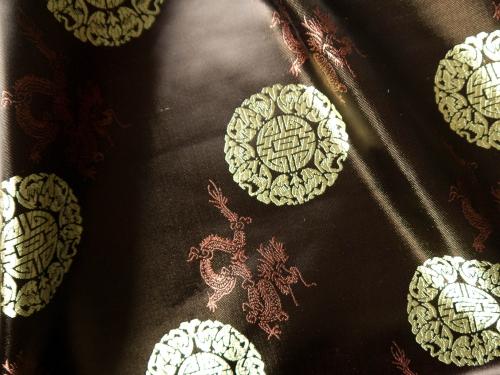 Jaquardstoff braun mit goldfarbenen Glückszeichen - Meterware