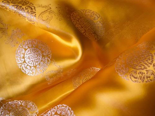 Dekostoff goldgelb mit Glückszeichen - Meterware