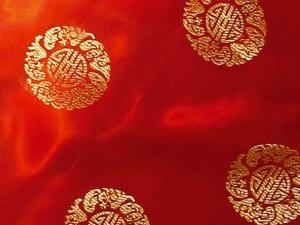 Jaquardstoff rot mit goldfarbenen Glückszeichen - Meterware