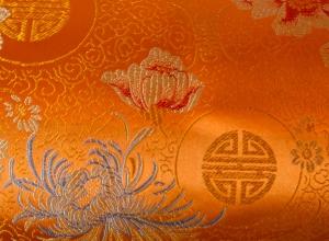 Jaquardstoff Glückszeichen orange mit Blumen - Meterware